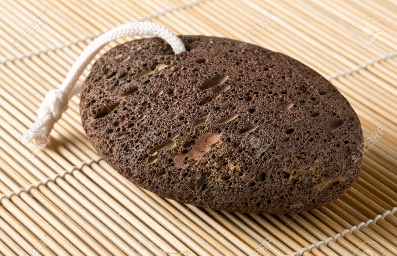 Black lava pumice stone spa or bath utensil used for peeling or callused skin removal on bamboo mat background - 138815500