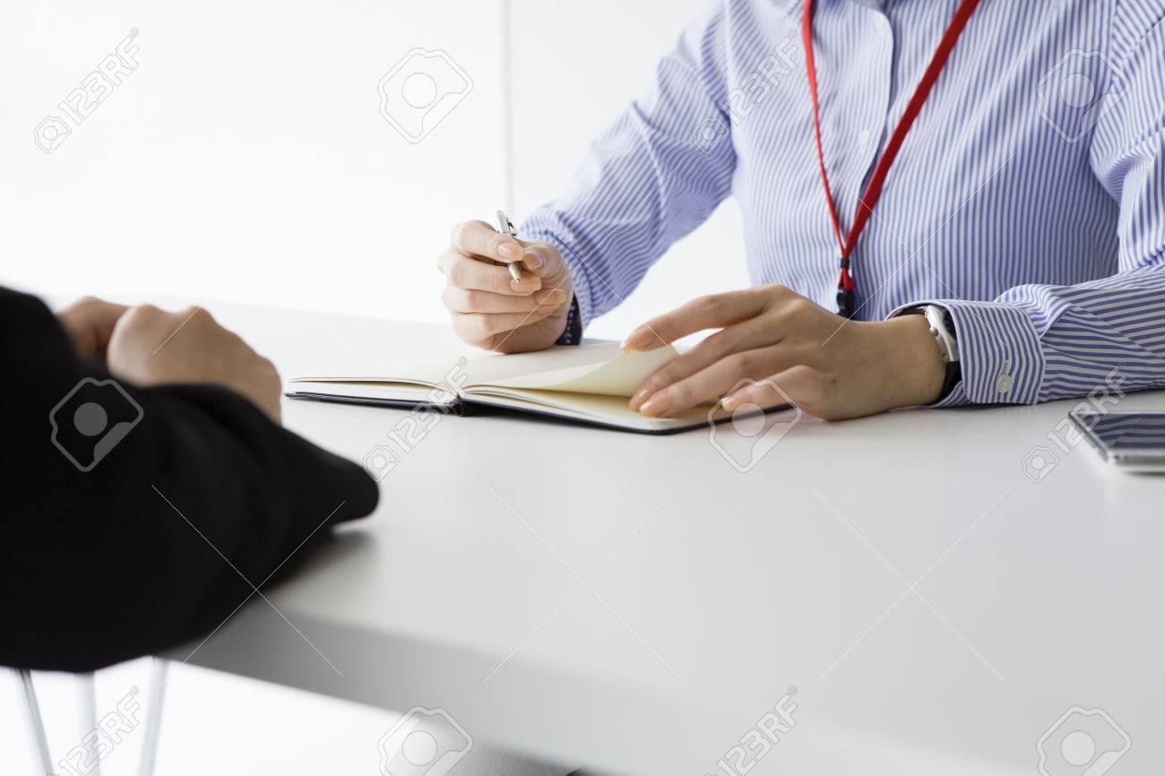 Businesswoman conducting a job interview seated at her desk in her office at the potential female candidate Stock Photo - 50252122