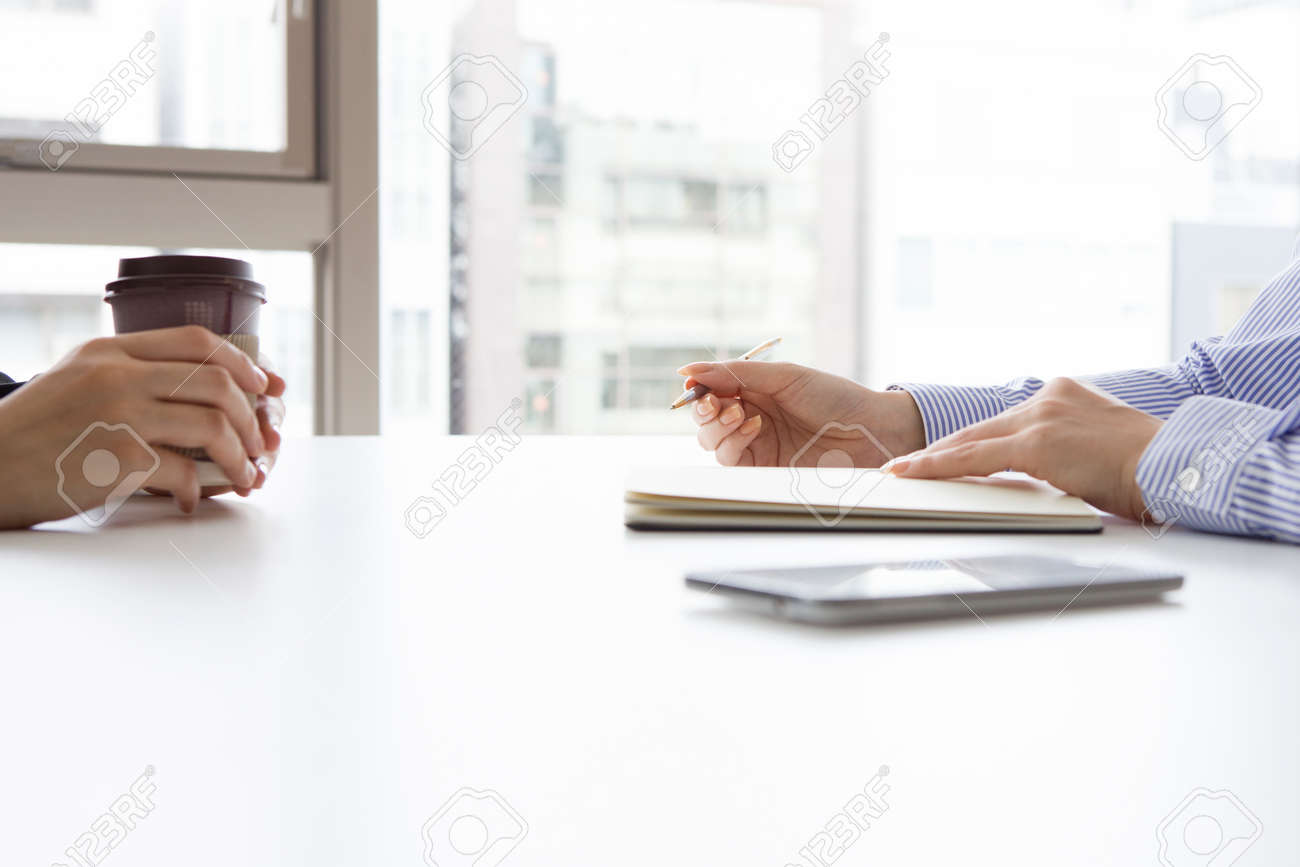 Businesswoman conducting a job interview seated at her desk in her office at the potential female candidate Stock Photo - 50363854