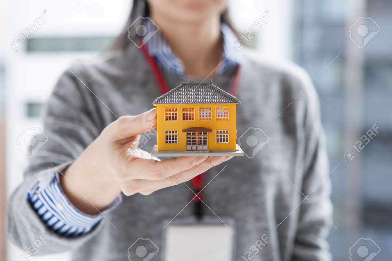 Real estate agent woman with a model of the house - 52808420