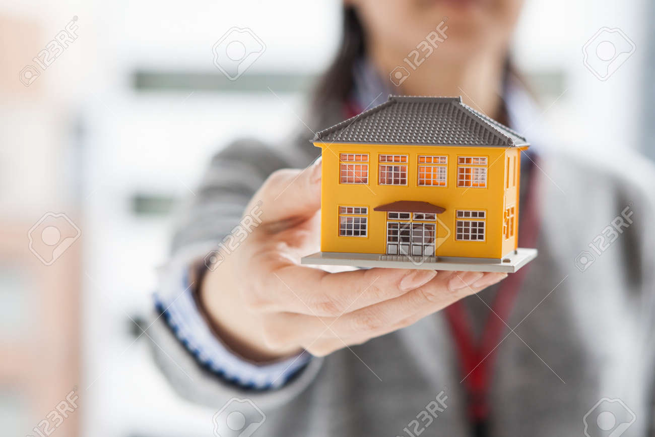 Real estate agent with a model of the house - 52808423
