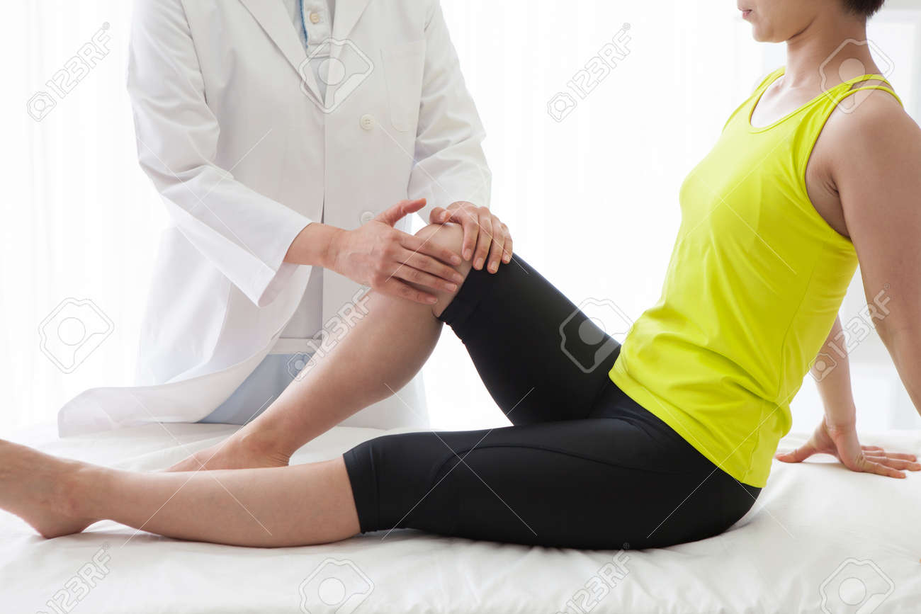 Masseuse stretching the right leg of a young woman. - 60456468