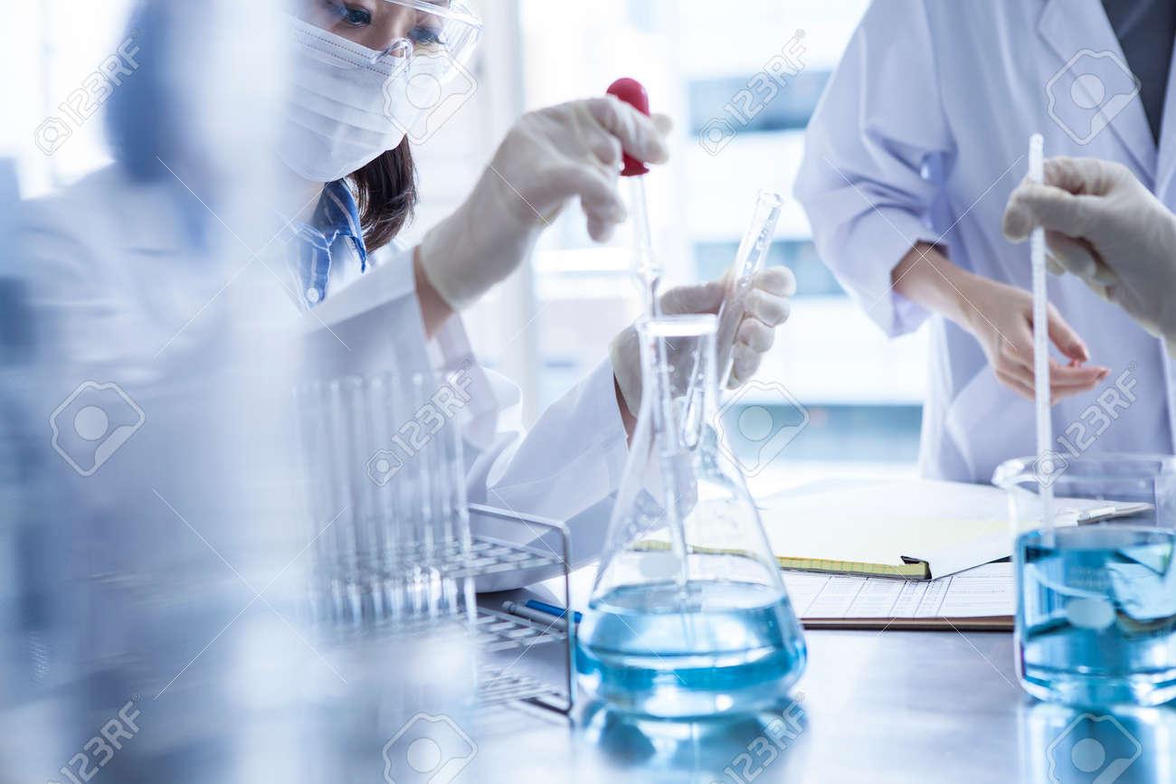 Scientist in laboratory examining liquid in Erlenmeyer flask. - 60458394