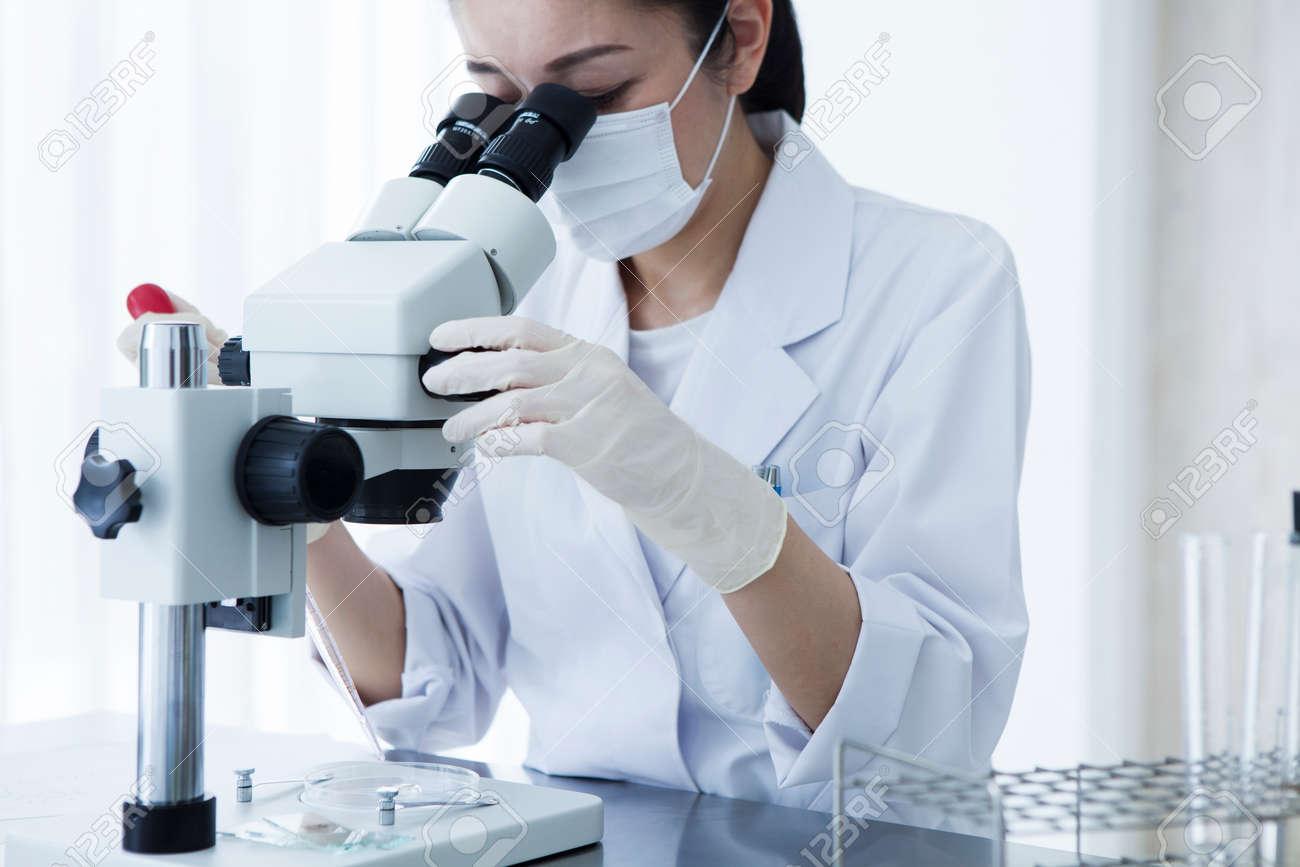 Microscope and female researcher. - 60458667