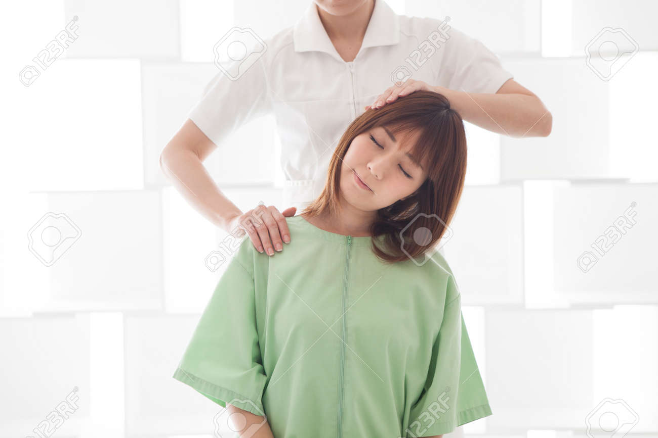 A woman sitting in bed and receiving shoulder and neck massage. - 87407791