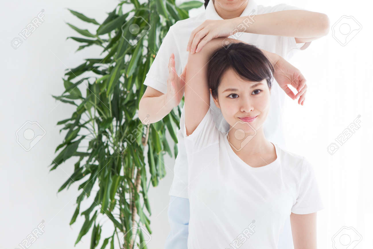 A woman sitting in bed and receiving shoulder and neck massage. - 88040943