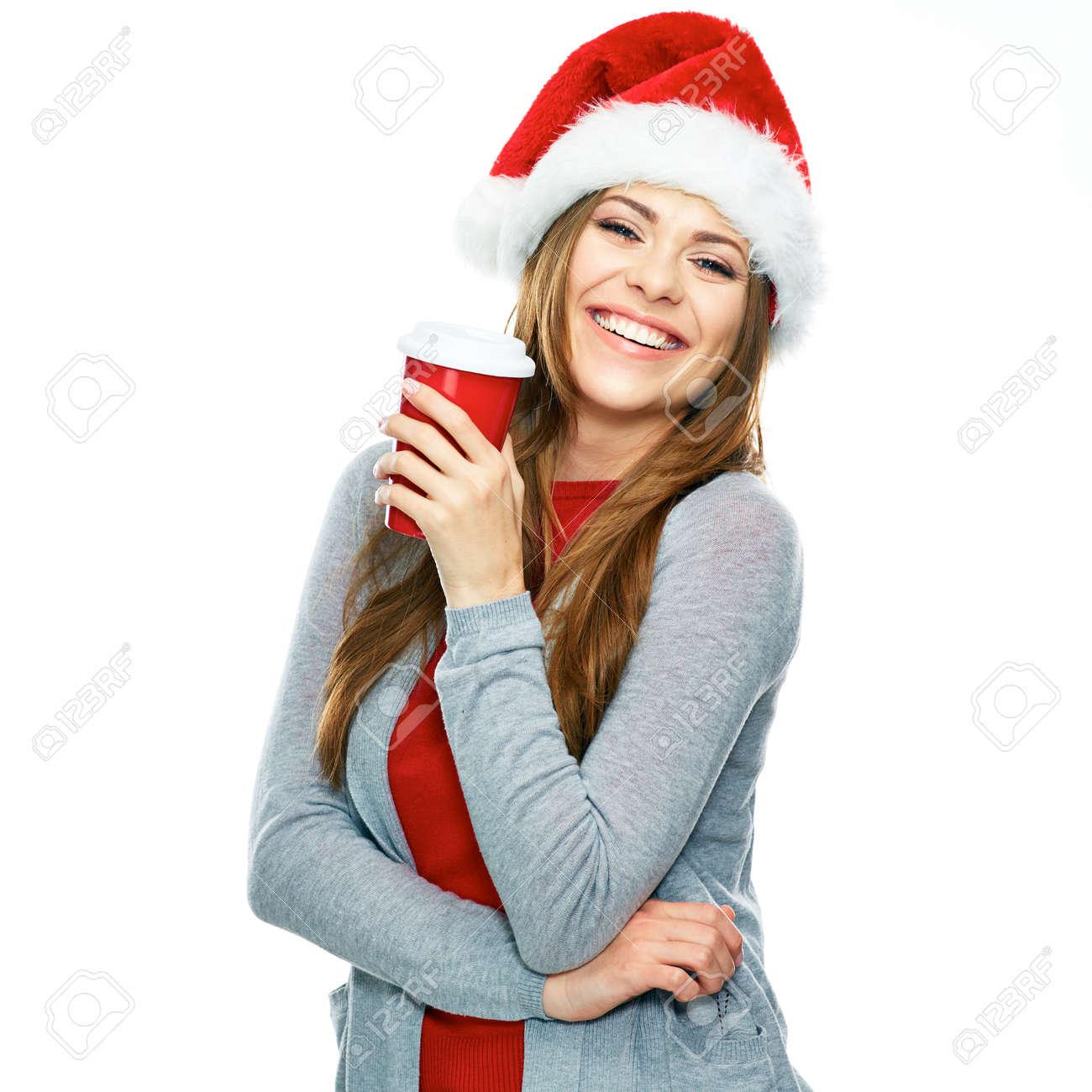 Archivio Fotografico - Ritratto di Natale di giovane donna con cappello  santa isolato su sfondo bianco. Tazza di caffè rosso 9994a093c9b1