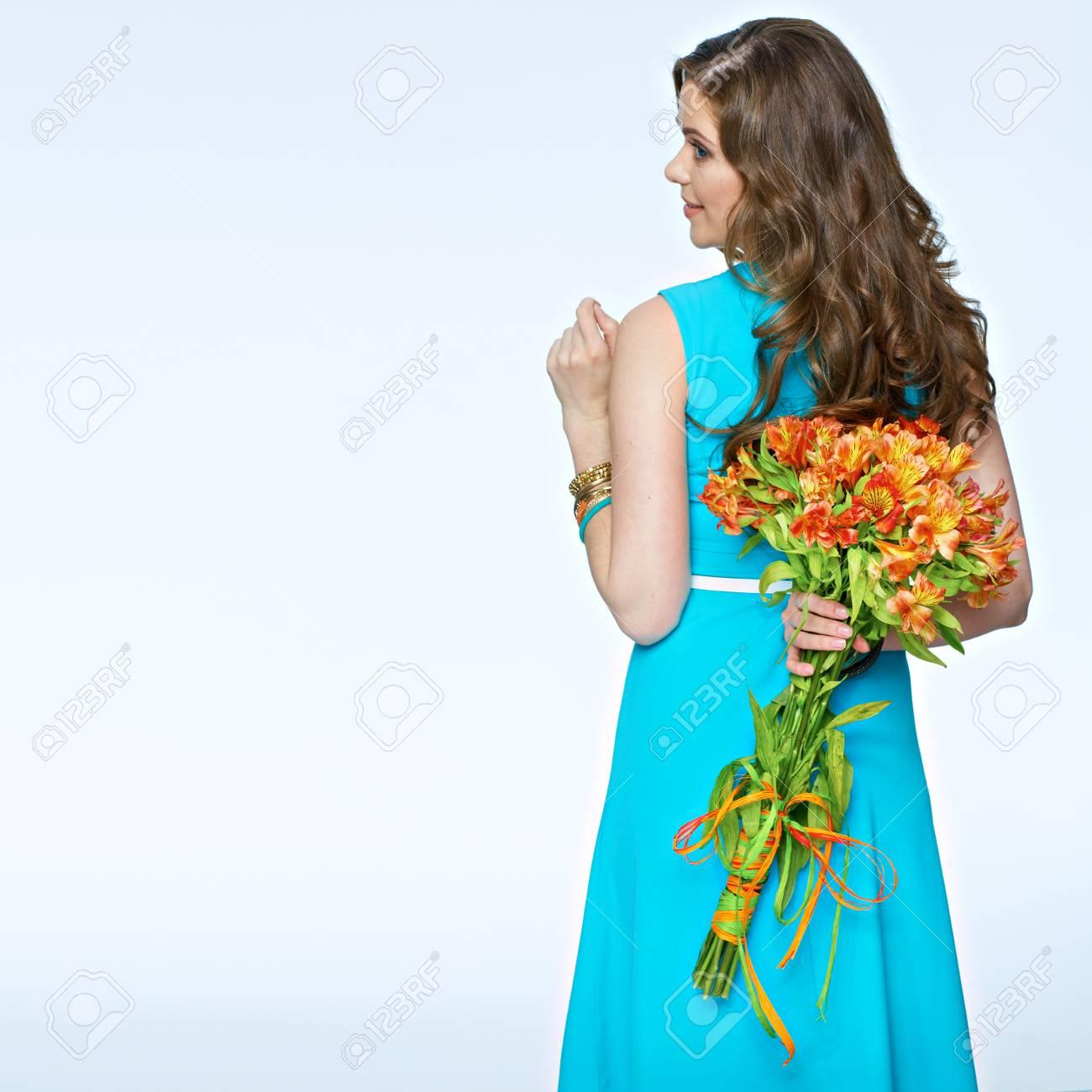 frau mit den blumen, die zurück auf weißem hintergrund stehen. lange haare.  blaues kleid.