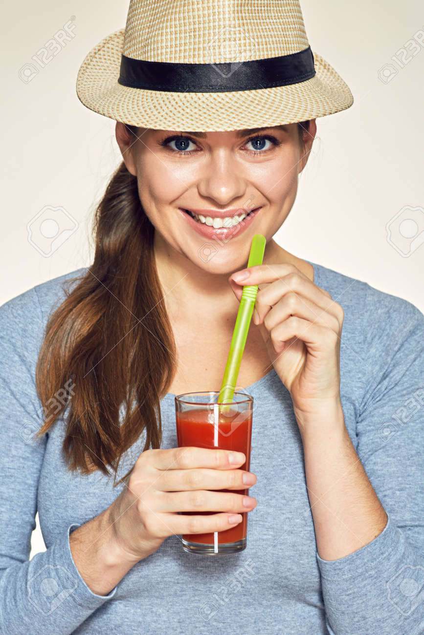 smiling woman holding red juce glass with straw wearing modern