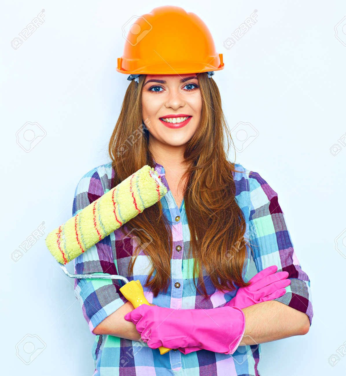 Young woman with crossed arms holding painting roller, standing against white background wall. Studio portrait of smiling woman. - 125068681