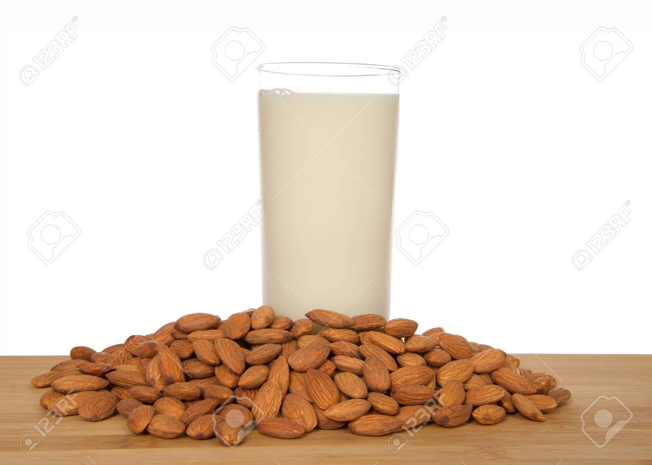 Glass of almond milk on a wood table surrounded by whole raw almonds, isolated on white background. Almond milk is lower in calories than other milks and cholesterol free, lactose free. - 116310886