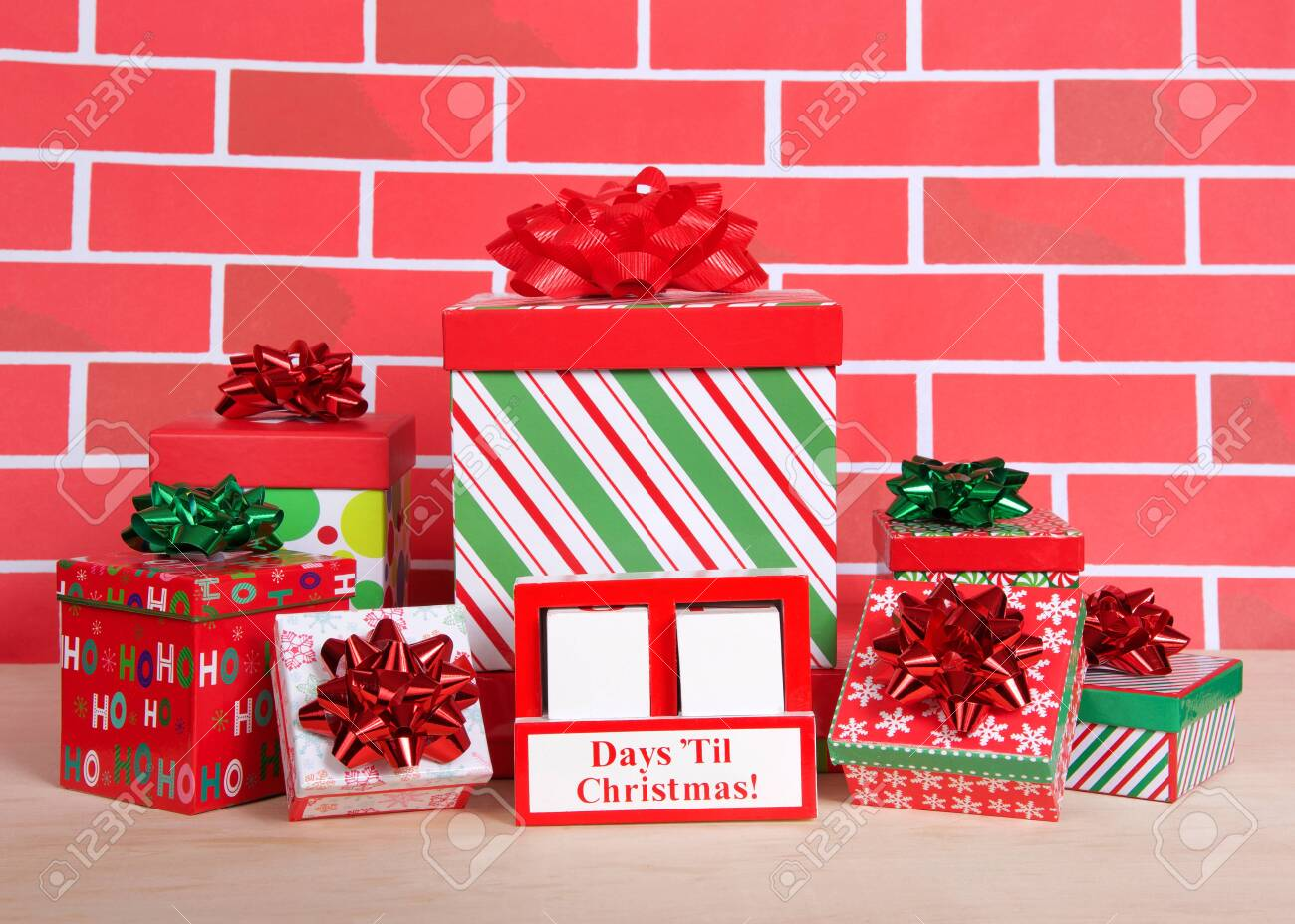 How many days til Christmas white wood blocks in a red box with presents stacked around it sitting on a light wood table with cartoonish brick wall background. Count down blocks blank to fill in days. - 154446988