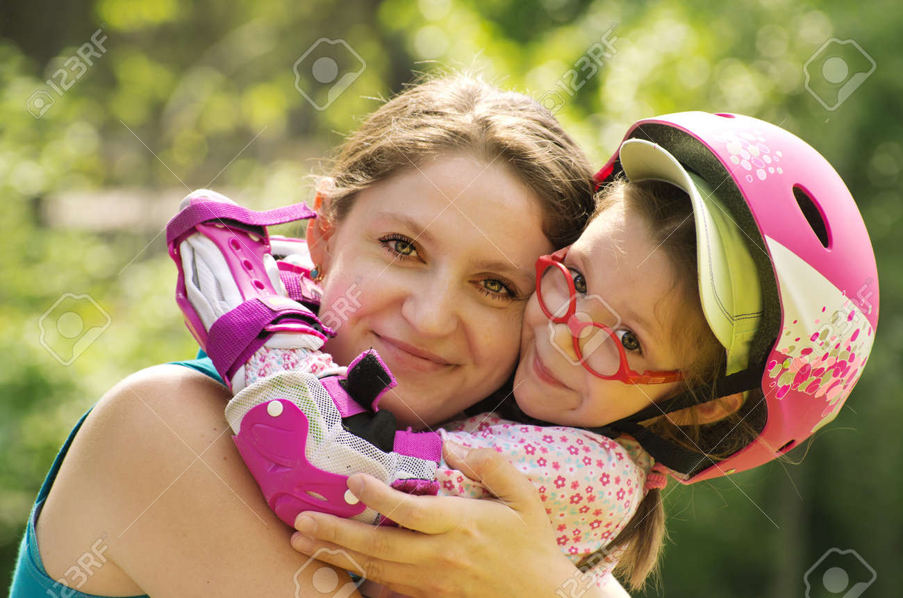 Outdoor portrait of caucasian mother and daughter wearing rollerblade protection and helmet. Stock Photo - 13621172
