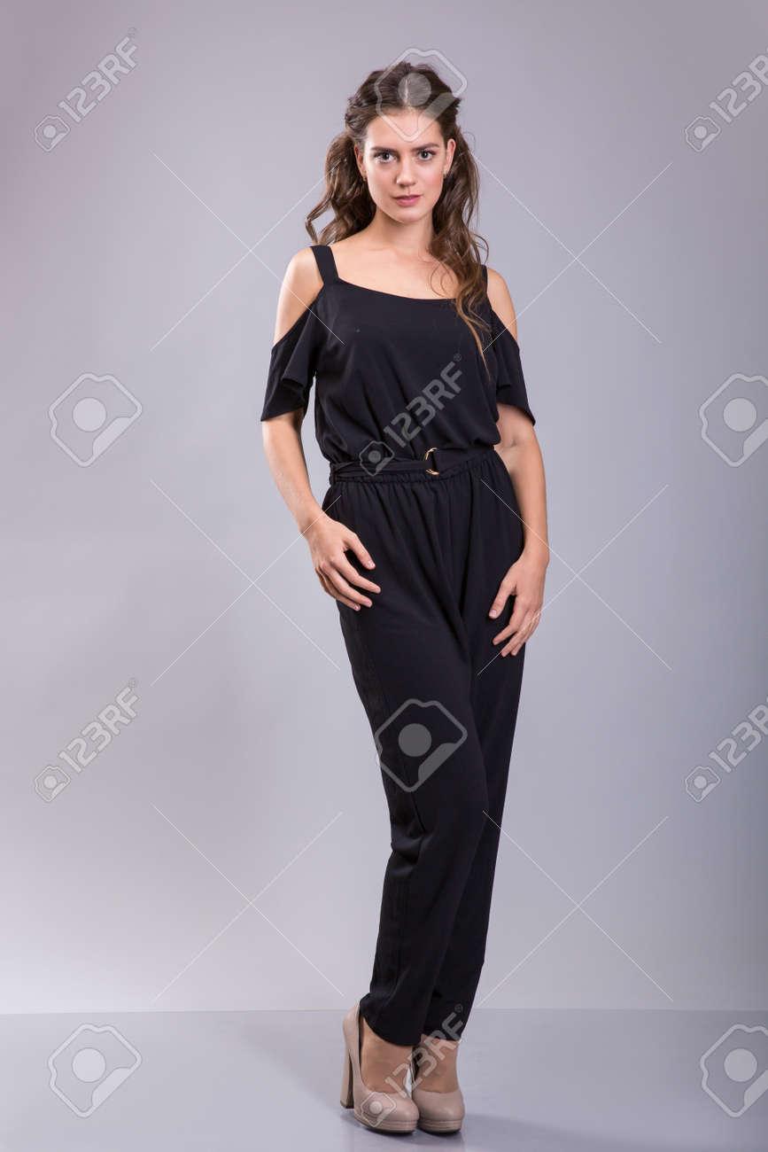 d1a2bbff6 Foto de archivo - Mujer morena en traje negro sobre fondo gris. Sesión de  estudio
