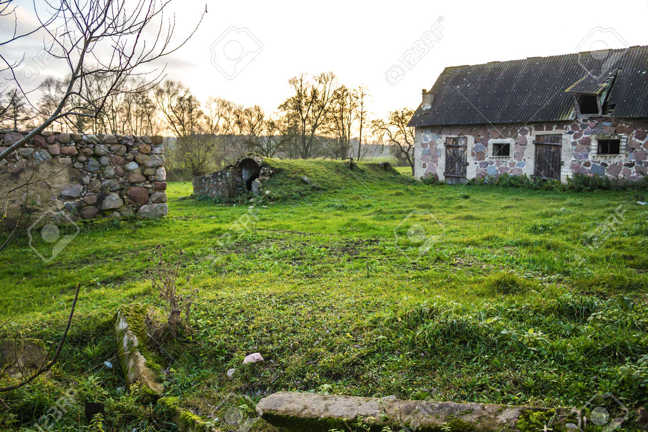 Stock Photo - The farmyard is an agricultural abandoned farm. The old collapsed barns. The entrance to the cellar is like a cave. The late autumm . & The Farmyard Is An Agricultural Abandoned Farm. The Old Collapsed ...