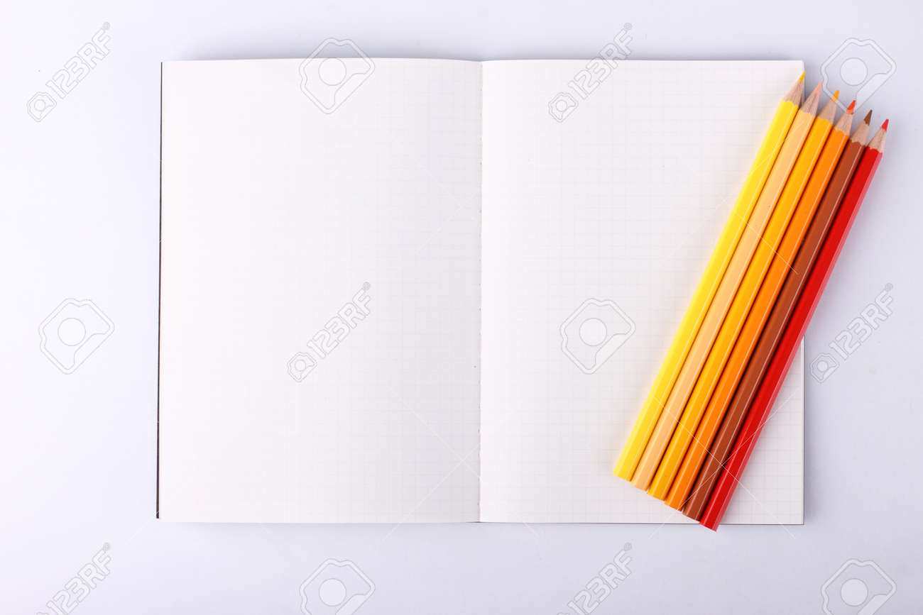 colour pencils with blank notebook isolated on white background