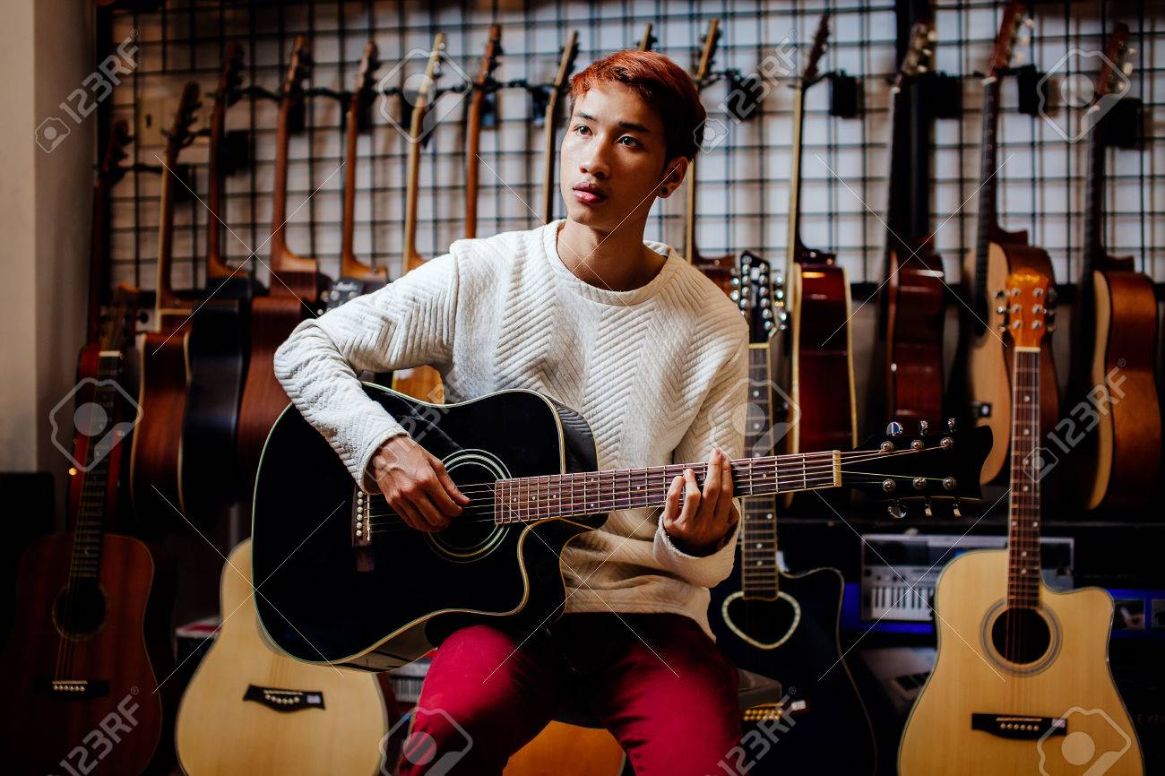 handsome asian teenage man playing acoustic guitar in guitar shop Stock  Photo   40354771. Handsome Asian Teenage Man Playing Acoustic Guitar In Guitar