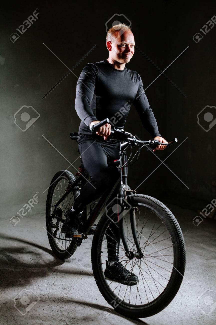 banque dimages homme de cycle vlo lintrieur lhomme en noir cyclisme vtements sur fond de mur gris