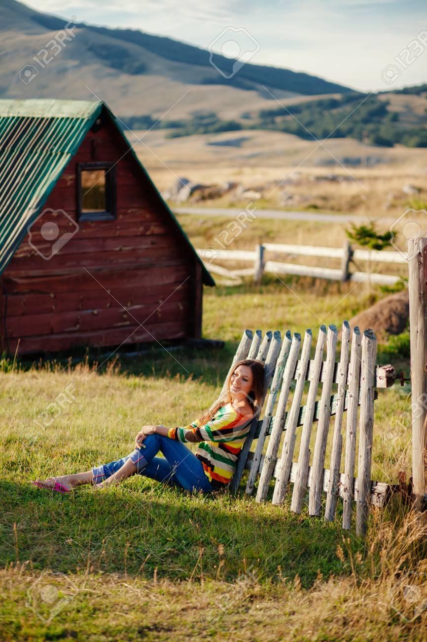 """Expresa tu momento """" in situ """" con una imagen - Página 31 75988009-mujer-relajarse-en-el-c%C3%A9sped-en-el-campo-casa-y-monta%C3%B1as-fondo-de-madera"""