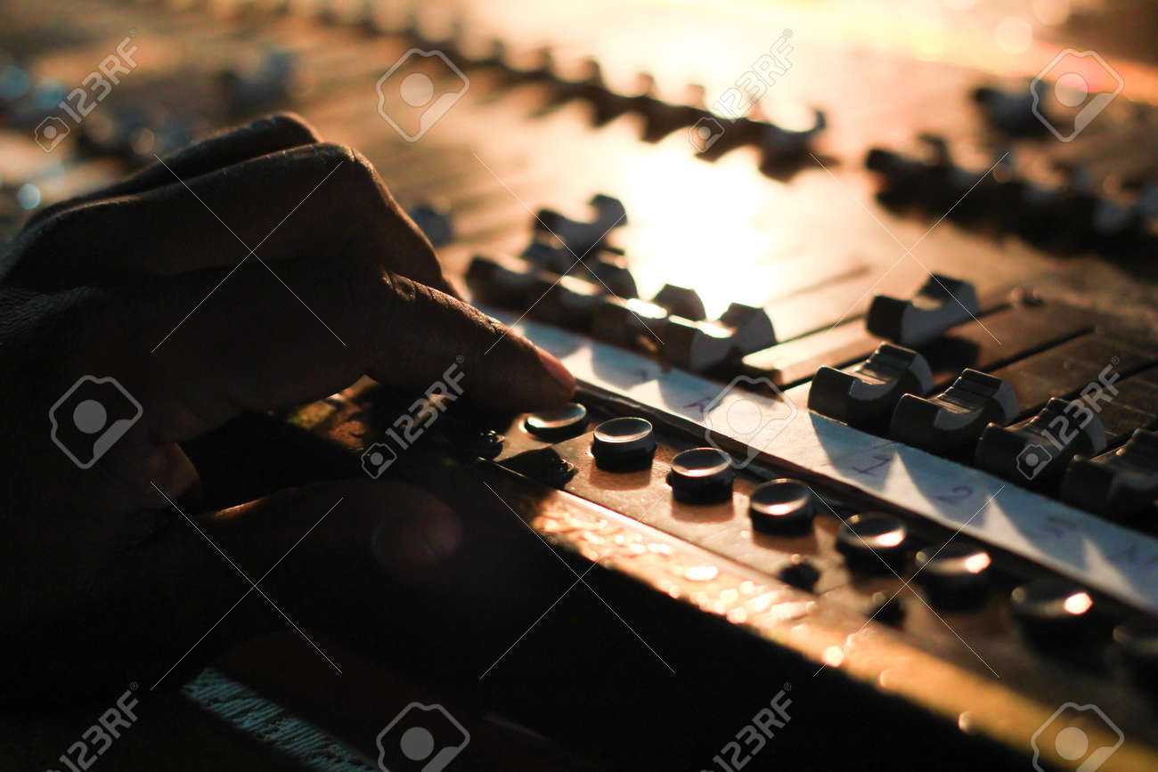 hands operating buttons of light and sound board console at a