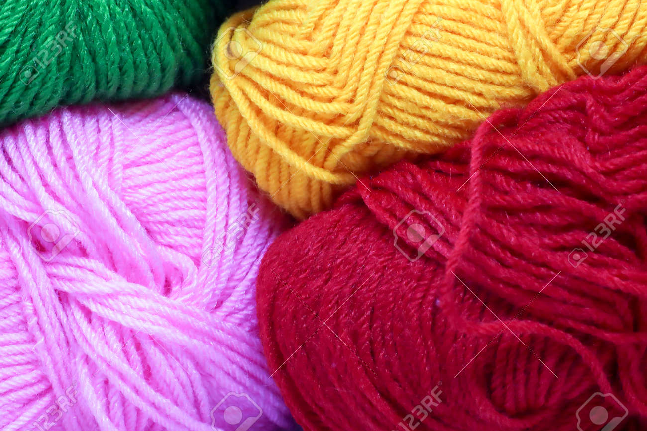 balls of pink green red yellow and white colored wool. - 135228899