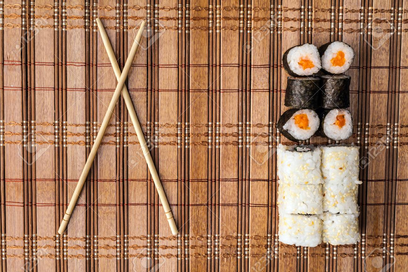 Chopsticks And Sushi Roll On Bamboo Mat Background Menu