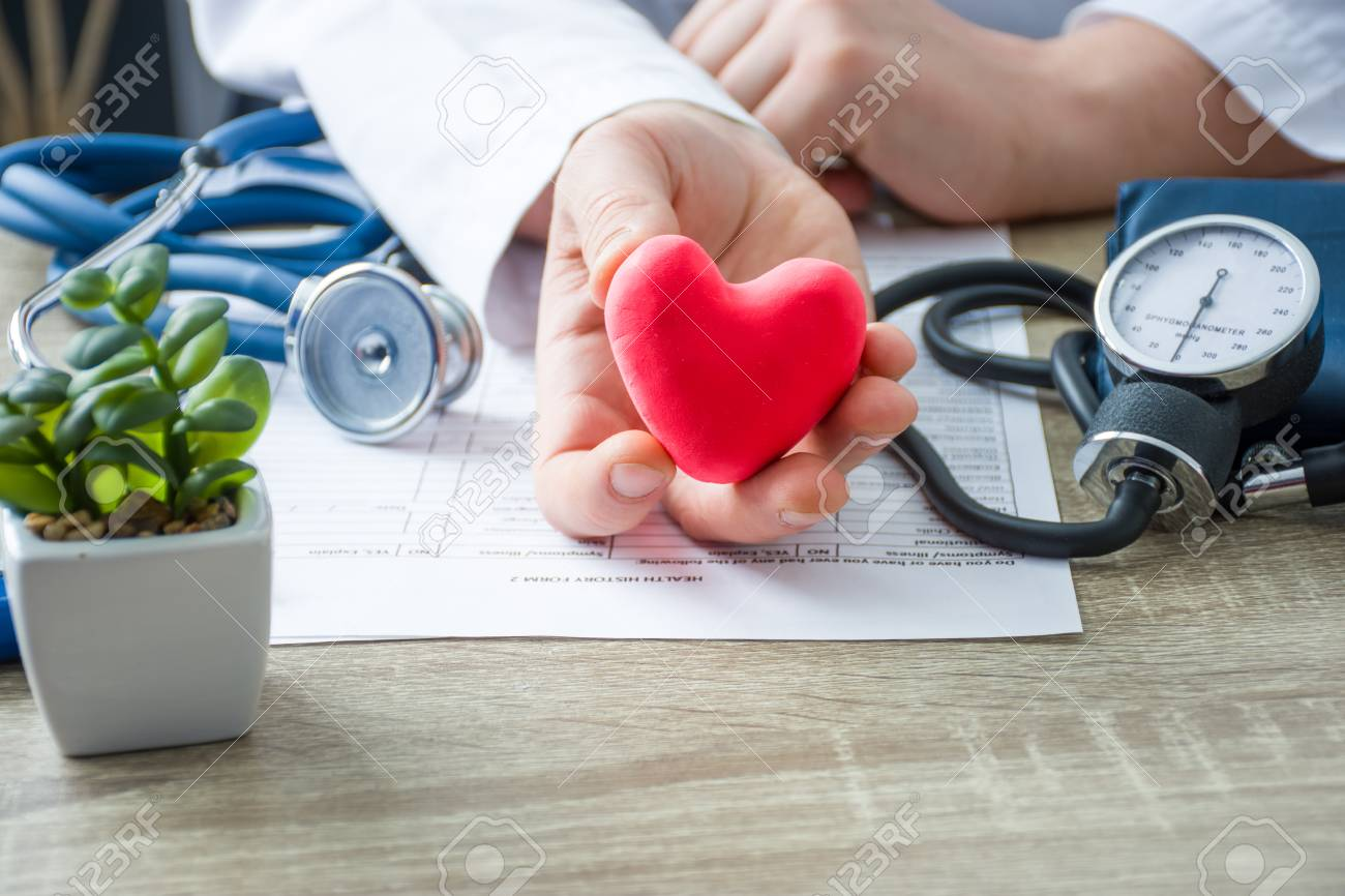 Doctor of internal medicine and cardiologist holding in his hands and shows to patient figure of red card heart during medical consultation. Explanation of causes of heart, diagnosis and treatment - 120977020