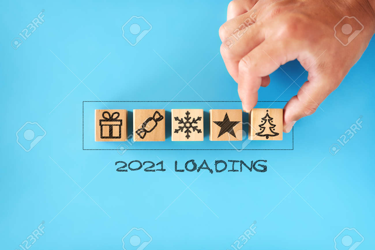 2021 loading. man stack wooden cubes with Christmas symbols - tree, gift, snowflake, in progress bar - 160691768