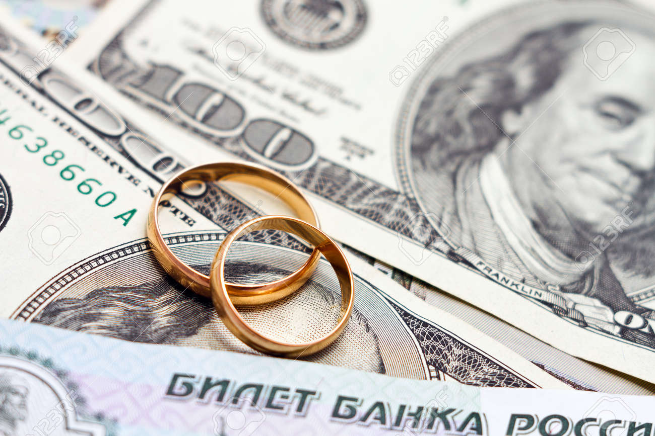 Wedding rings, gold chain and earrings in the form of hearts lie on money Standard-Bild - 21066255