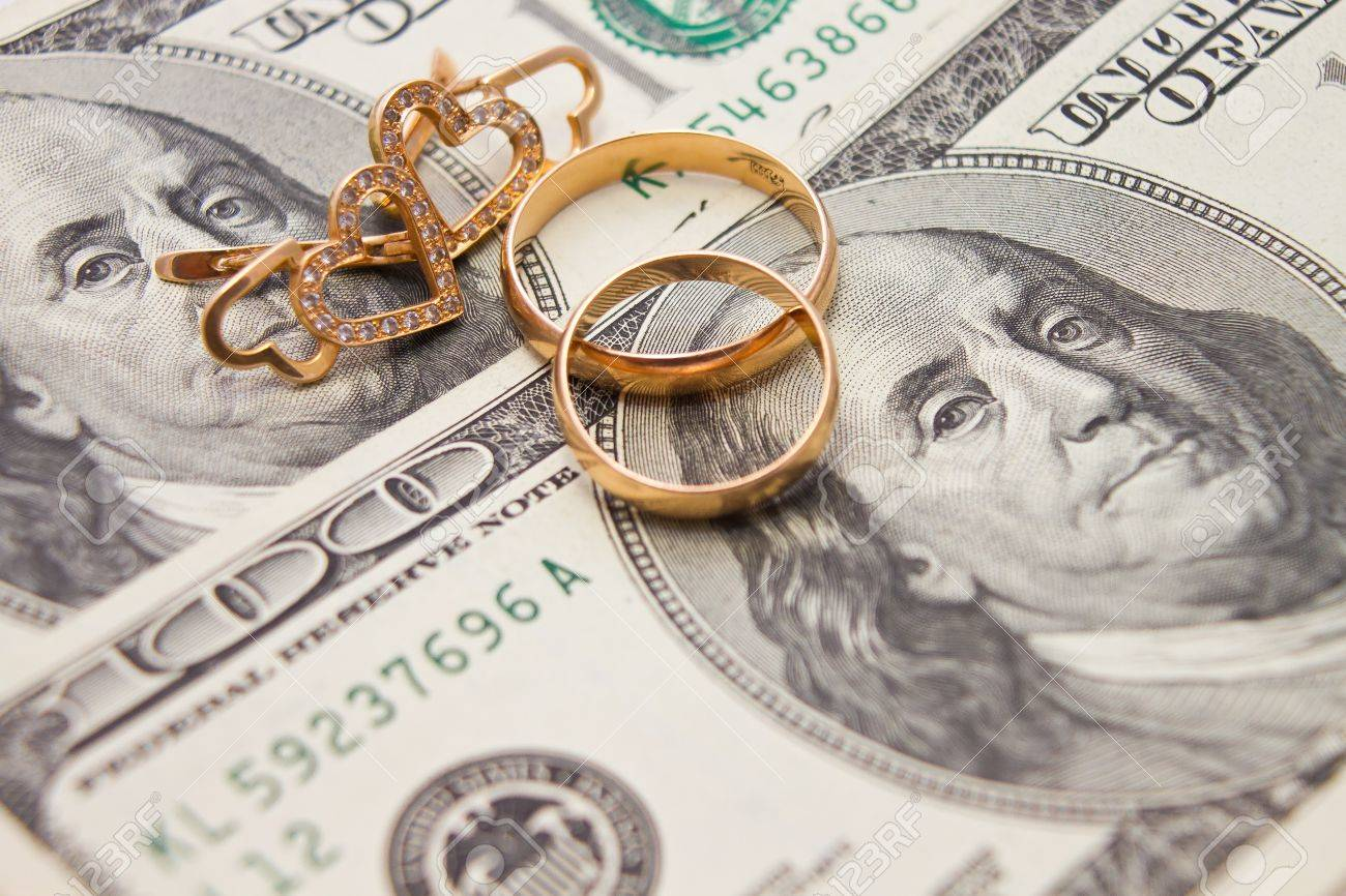Wedding rings, gold chain and earrings in the form of hearts lie on money Standard-Bild - 21066266
