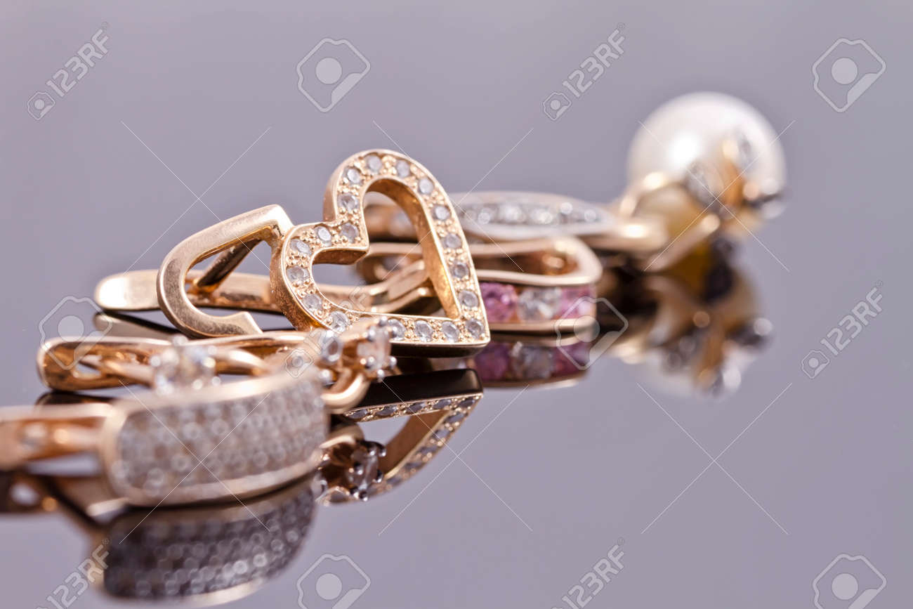 variety of gold earrings with various inserts lie in a line on the reflecting surface Standard-Bild - 39440598