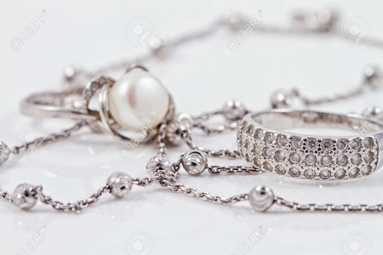 Silver ring with precious stones and pearl are together with a silver chain on acrylic Standard-Bild - 44106520