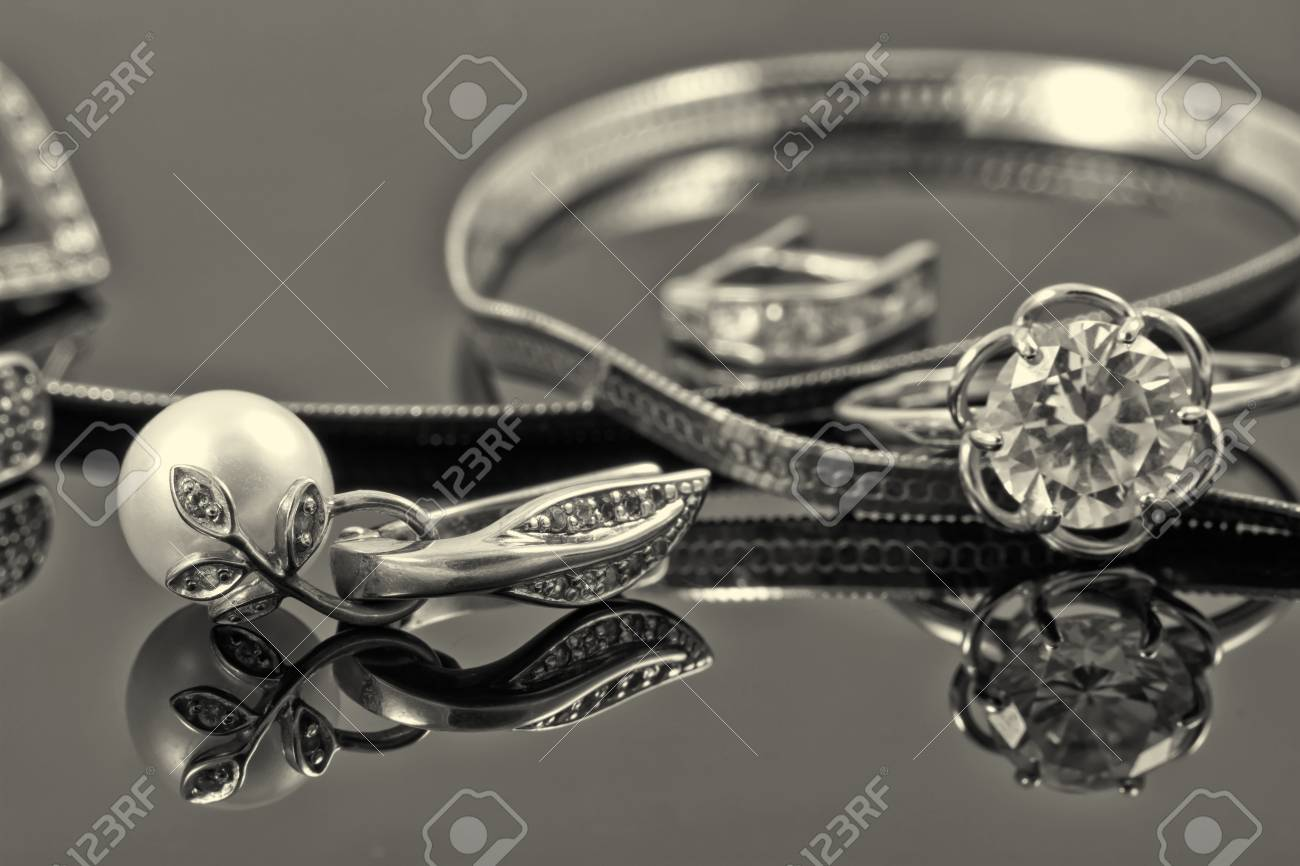 gold ring, earrings and chains on a reflective surface Standard-Bild - 44432118