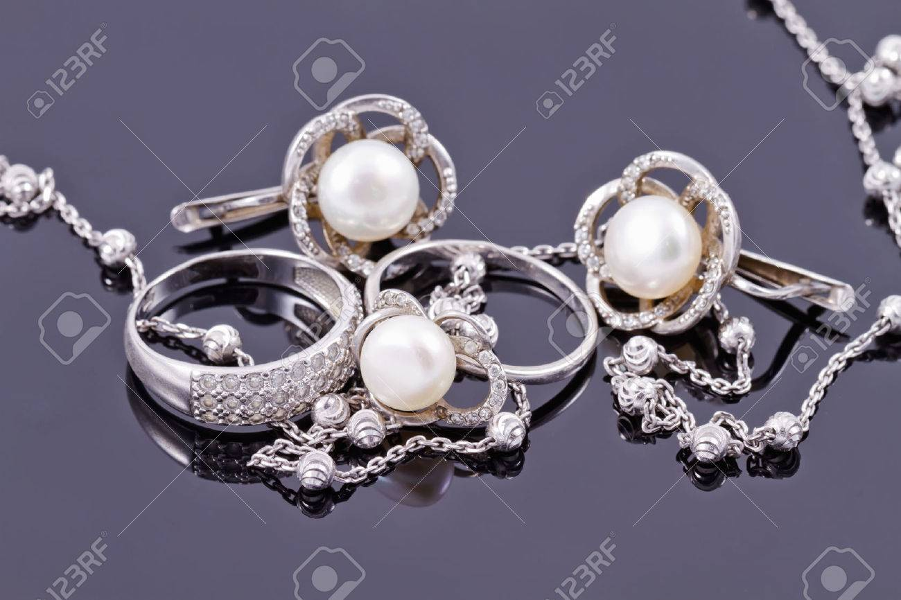 Fine silver rings are together with unusual silver chain on a white acrylic Board Standard-Bild - 45646895