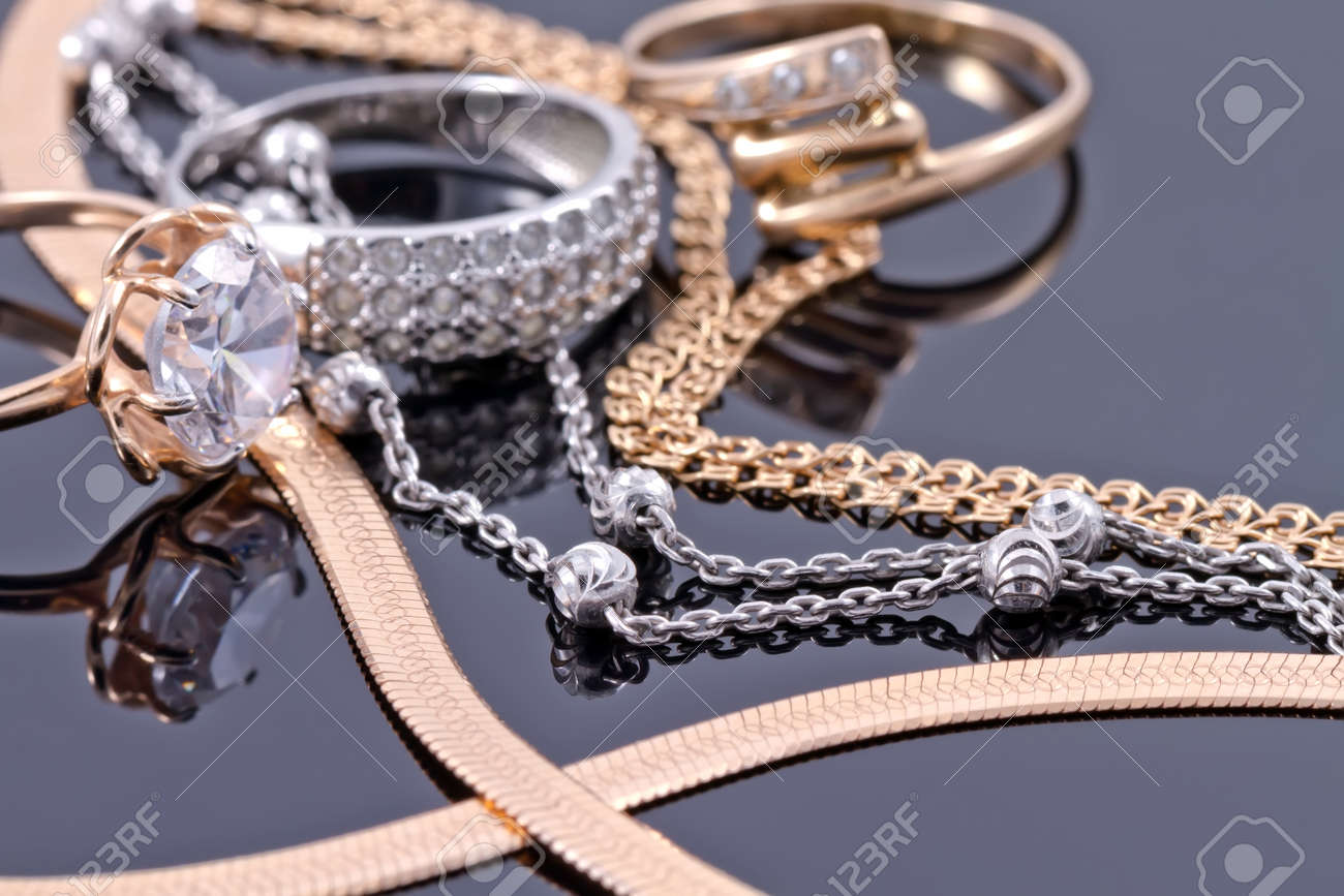 Gold, silver rings and chains of different styles are lying together on the reflecting surface Standard-Bild - 45646964