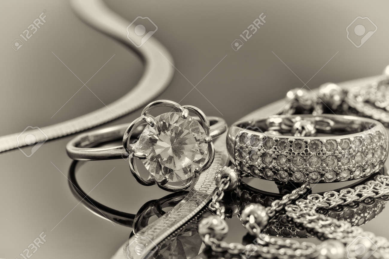 Gold, silver rings and chains of different styles are lying together on the reflecting surface Standard-Bild - 46325288
