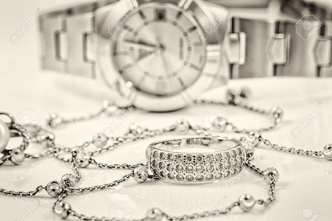 Silver ring and chain on the background of women's watches Standard-Bild - 46325306
