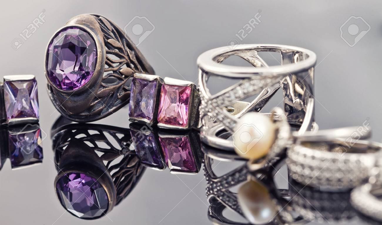A set of silver jewelry from chains, rings, signet rings and bracelet with purple gemstones Standard-Bild - 49973822