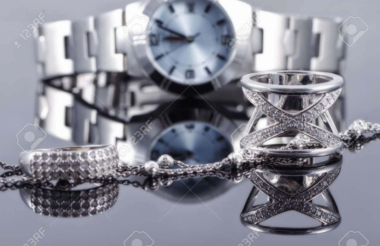 Silver rings of different styles and silver chain on the background of reflections women's watches Standard-Bild - 50331115