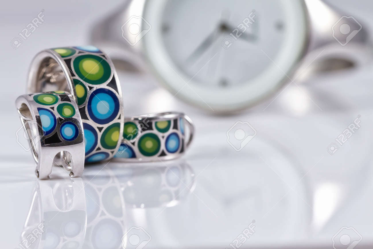 silver jewelry with pearls on a background of elegant women's watches Standard-Bild - 50584922