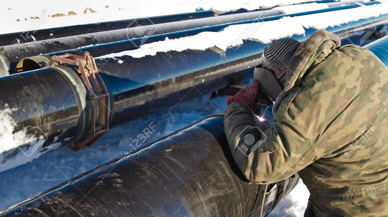 Stock Photo - welder performs welding of pipe insulation on the pipeline route high pressure in winter conditions & Welder Performs Welding Of Pipe Insulation On The Pipeline Route ...