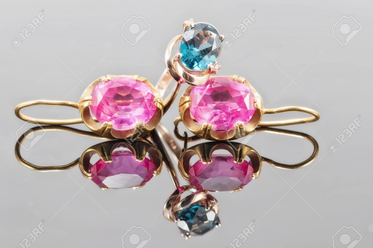 d84cdd1c8182 Anillo de oro con el color topacio azul Londres y pendientes con rubíes  grandes en la