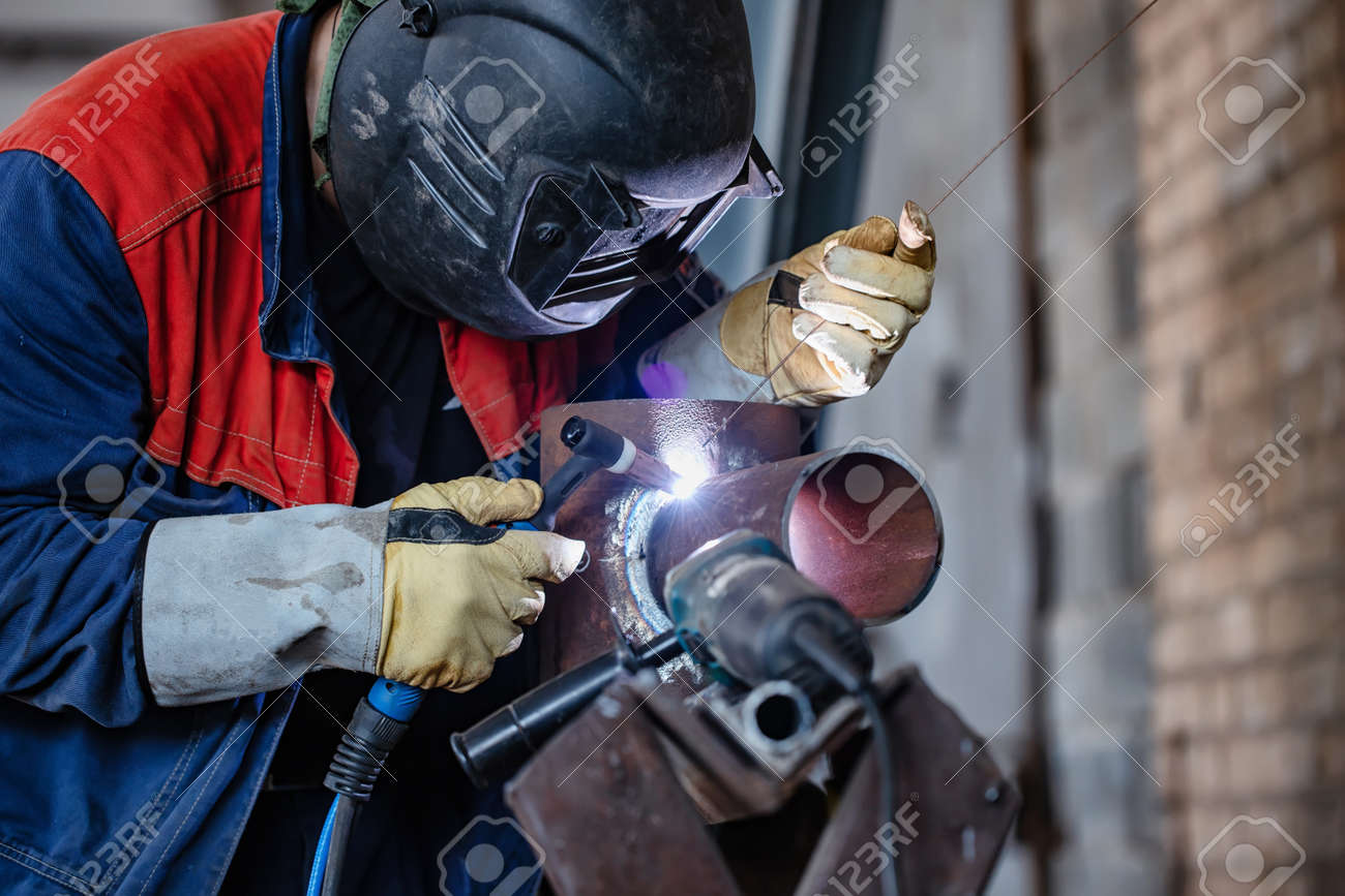 Welder in the shop weld sample from the tube for passing of certification. Manual arc welding using remote control - 129459844