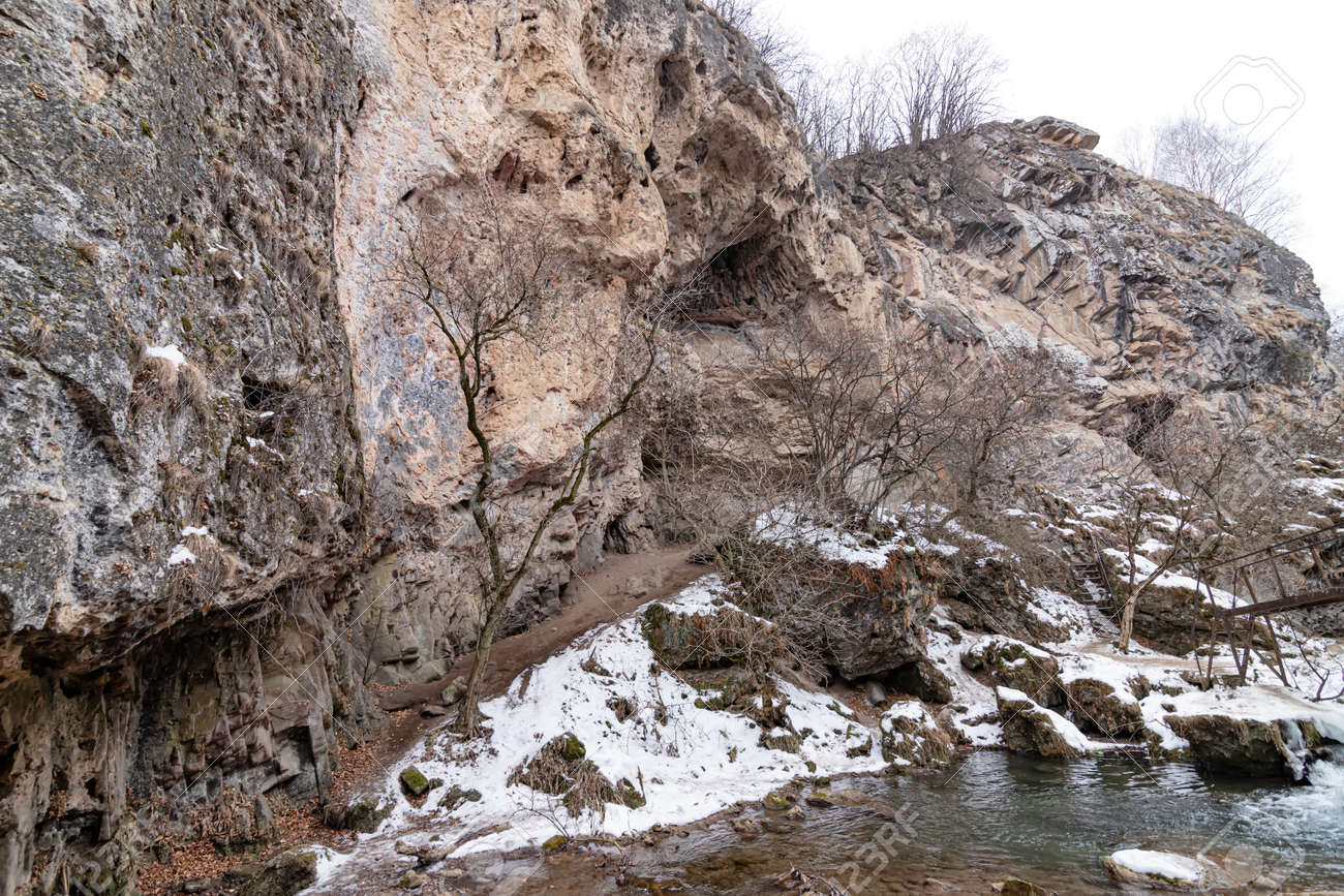 The waterfalls, which are not completely frozen in winter, flow down from the porous rocks - 163595707