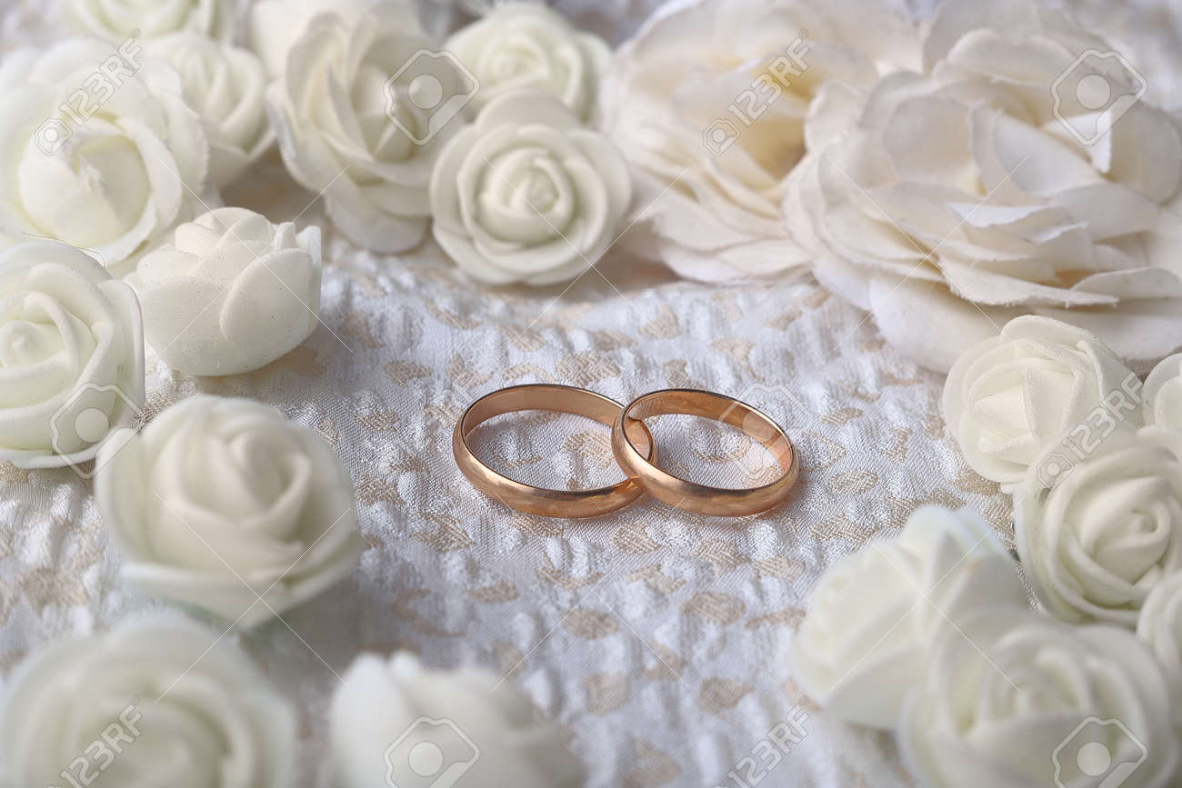 Gold wedding rings on beige fabric decorated with beige artificial flowers - 159076825