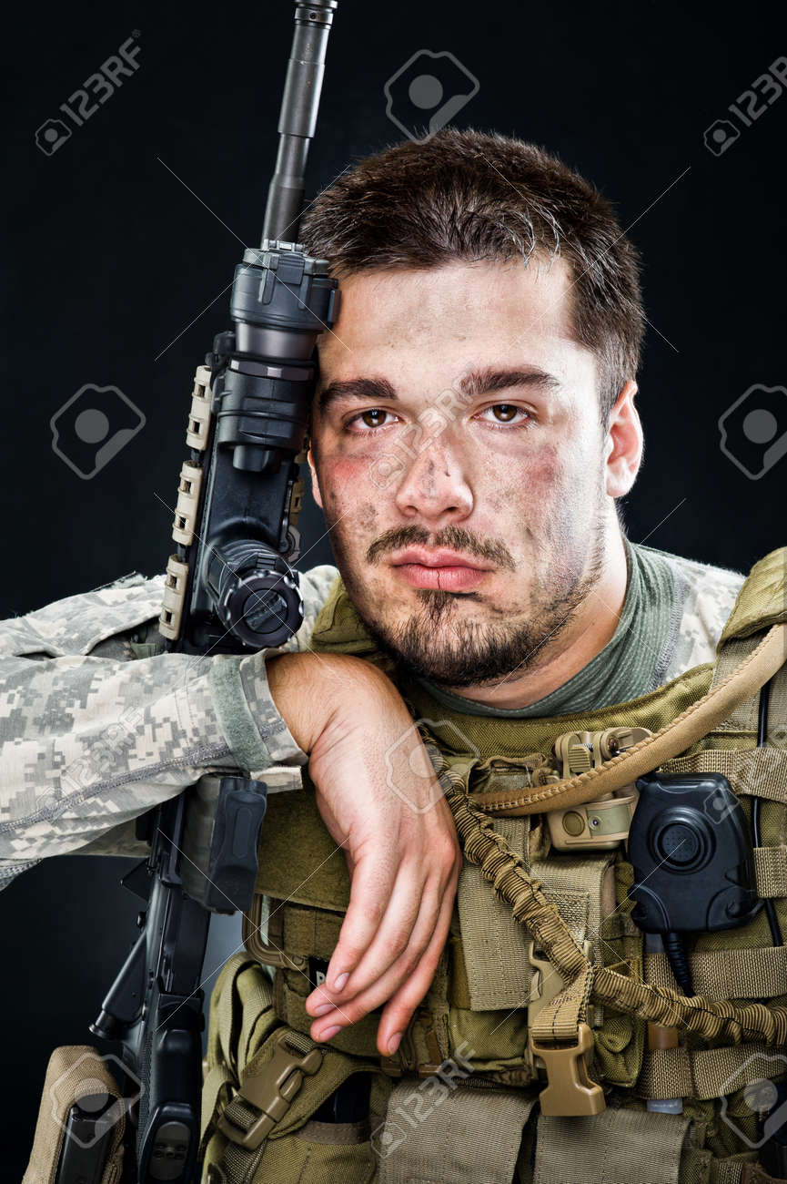 Soldier of USA army posing with a gun on a black background - 11890124