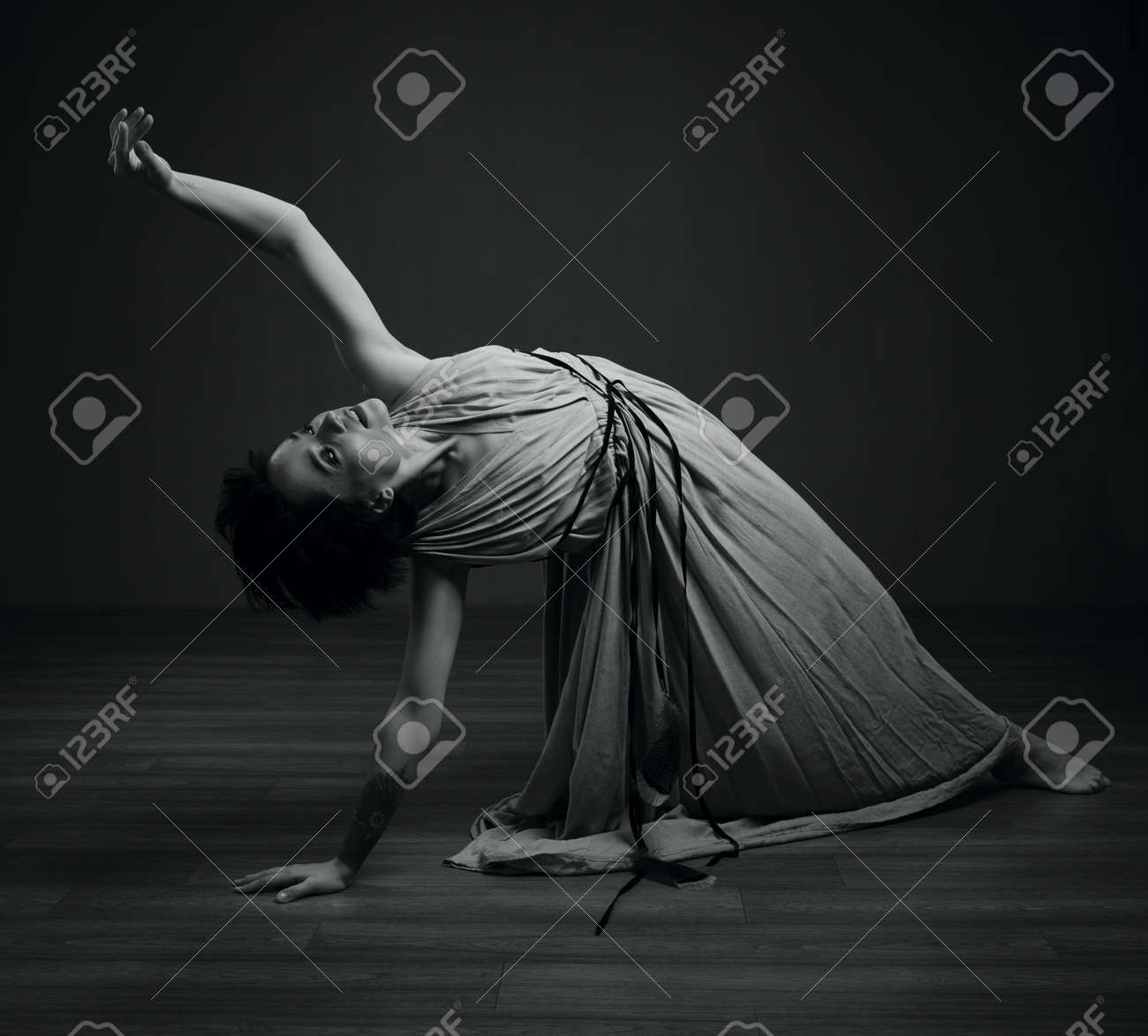 Black and white dancing woman studio portrait on a dark background