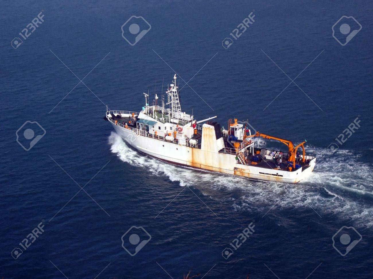 Ship at Sea -- a medium sized vessel is heading out to sea Stock Photo - 2527475