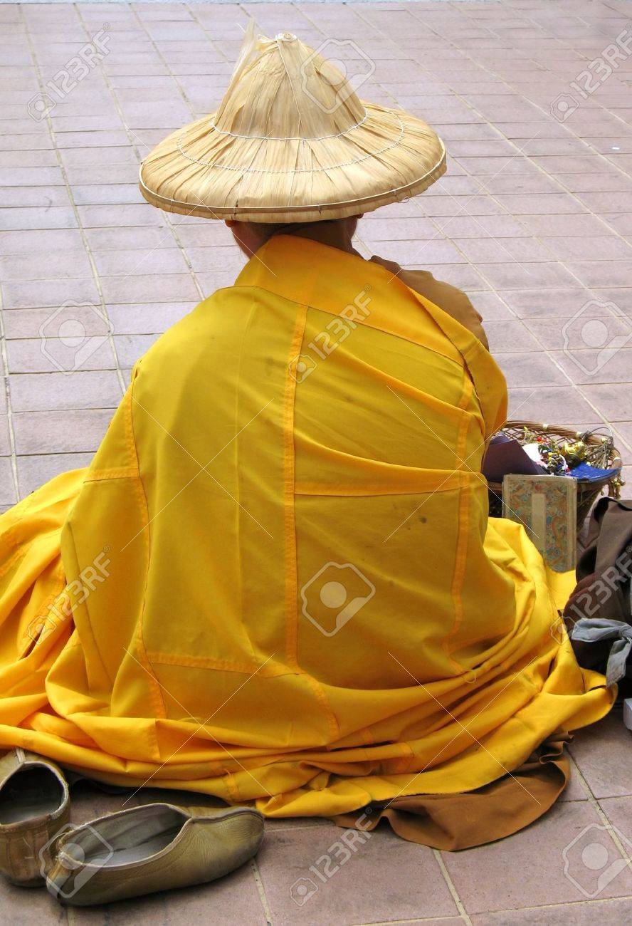 Buddhist Monk ,, in yellow robe, begging for alms and selling trinkets Stock Photo