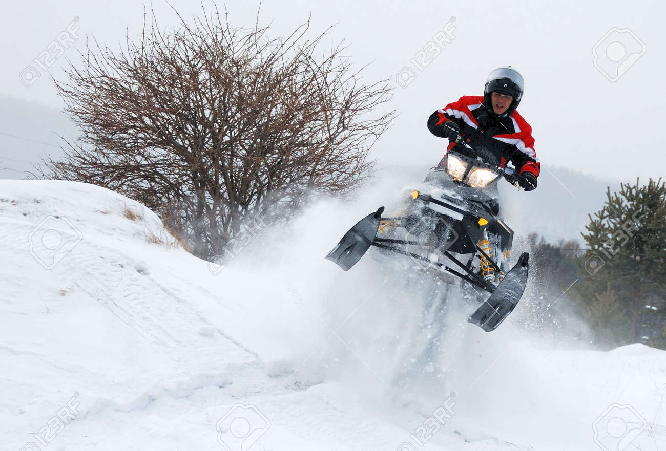 Young man driver on the black-yellow snowmobile jumping high Stock Photo - 6453931